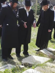 Rabbis discuss over the historic gravestones from the old cemetery.